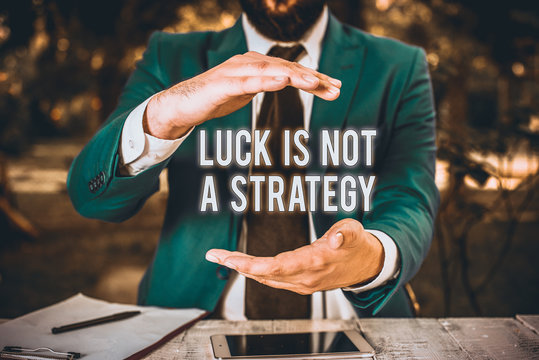 Conceptual hand writing showing Luck Is Not A Strategy. Concept meaning it is not being Lucky when planned intentionally Man in front of table. Mobile phone and notes on the table