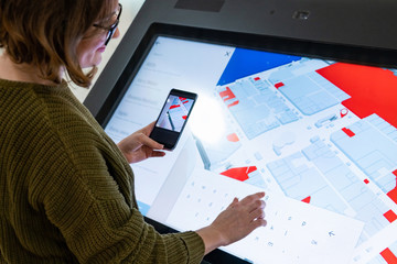 Woman with phone uses self-service kiosk in the shopping mall Wall mural