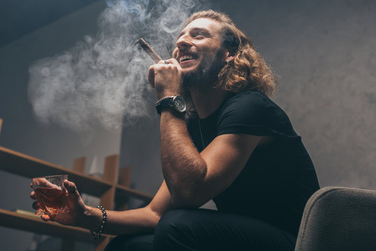 low angle view of smiling fashionable businessman in black outfit smoking cigar and drinking whiskey