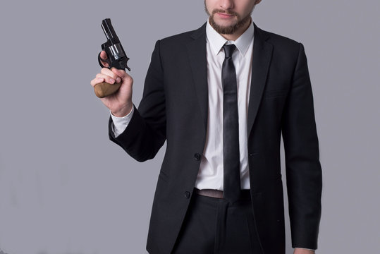 Portrait of a bearded man in a business suit holding a revolver. On a gray background.