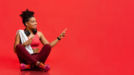 Cheerful fitness model sitting on floor, pointing at free space