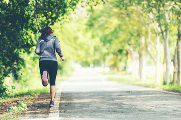 Foto op Plexiglas Jogging Sporty asian woman runner running and jogging through the road. Outdoor Workout in a Park. Weight Loss and Healthy Concept