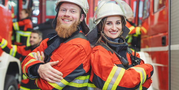 Fire fighter man and woman standing shoulder to shoulder
