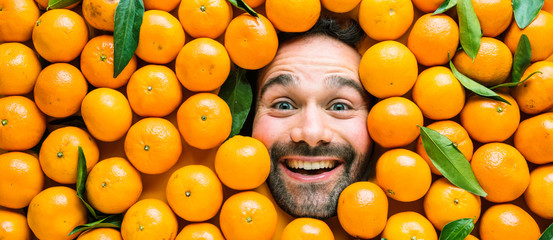 Man with ripe oranges, concept for food industry. Face of grimacing man in oranges or mandarins area  Fotomurales