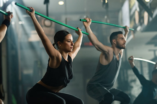 Athletic people exercising with rods on cross training in a gym.