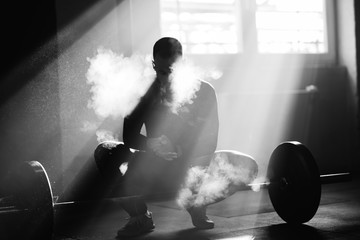 Sportsman applying talcum powder on his hand before weightlifting in a gym.