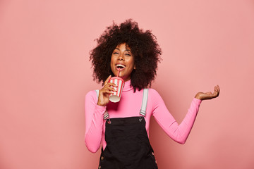 Joyful young African American female with curly hair wearing pink turtleneck and black overall holding white and pink striped disposable cup with straw and looking at camera