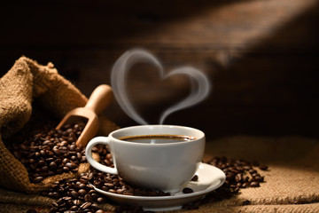 Spoed Fotobehang Cafe Cup of coffee with heart shape smoke and coffee beans on burlap sack on old wooden background