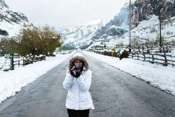 Focused female in white winter jacket with hood and black pants taking picture with camera while standing in middle of asphalt road between snowy mountains