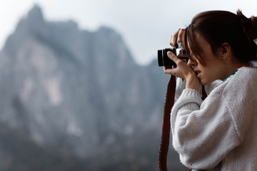 Side view of woman traveler in casual plaid shirt taking photo from opened window of nature at Dolomites mountains, Italy