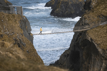 From above side view of traveler passing over Carric a Rede rope bridge suspended between rocky cliffs and sea waves crashing on rocks in background