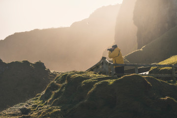 Side view of man traveler in warm activewear standing on rural road running along shore with green grass and taking photo with professional camera of ocean with calm water in sunny spring day in Northern Ireland
