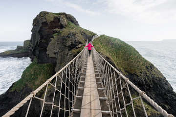 Back view of unrecognizable woman tourist in red jacket walking on rope Carric a rede bridge suspended between mainland and small rocky island at Northern Ireland coastline