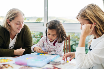 Middle aged woman with little girl and adult daughter having fun and playing board game creating picture with colorful mosaic pieces while sitting at round table on terrace