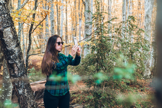 Woman in plaid shirt taking photo of autumn trees on mobile phone with woods on blurred background
