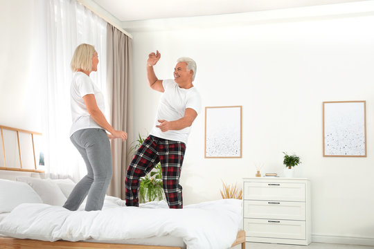 Happy mature couple dancing together on bed at home