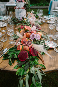 Beautiful garland made from ripe cut tropical fruits and green branches with flowers and decorative plants setting on round wooden wedding table served with plates and glasses