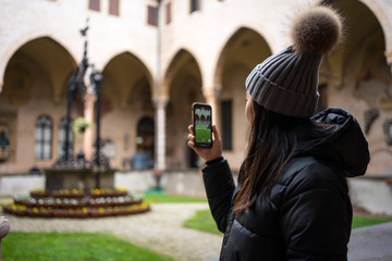 Side view of Asian female tourist in warm clothing and hat taking picture on mobile phone while exploring ancient Basilica of San Antonio at Padova at Italy
