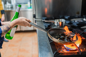 Chef cooking with flame in frying pan