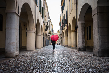 Back view of unrecognizable traveler in warm clothing sightseeing using red umbrella with old buildings on blurred background at Padova at Italy