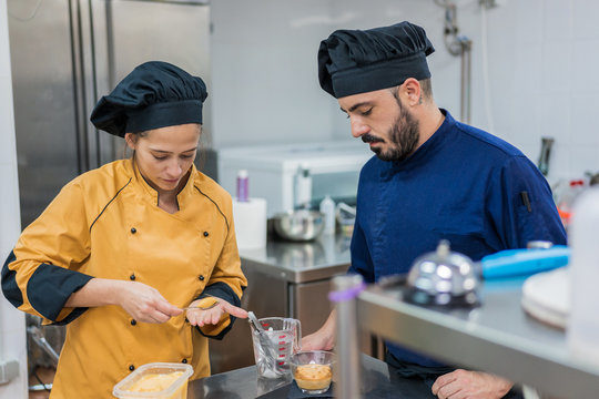 Cook with colleague serving food on plate
