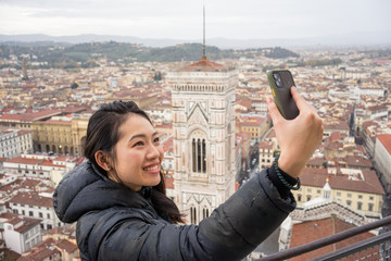 Happy Asian female smiling taking a selfie with mobile phone while standing on Brunelleschi Dome against old Florence streets during trip in Italy