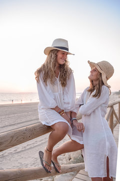 Charming relaxed women in white dresses and hat smiling while speaking comfortable placing on wooden fence on sandy beach in sunny day