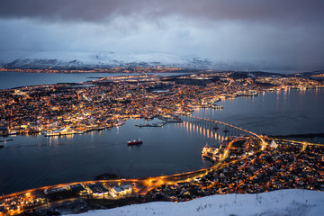 Magnificent scenery of city with golden lights located on island and shores of strait against foggy hills covered with snow under lush clouds in winter night Fotomurales