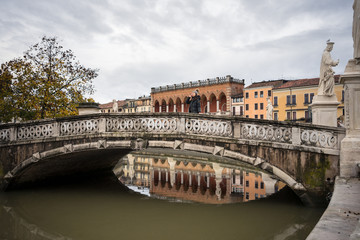 Foto op Plexiglas Historisch mon. Tourist in warm clothing on rocked ancient bridge above pond with old buildings and statues on background at Prato della Valle park at Padova at Italy