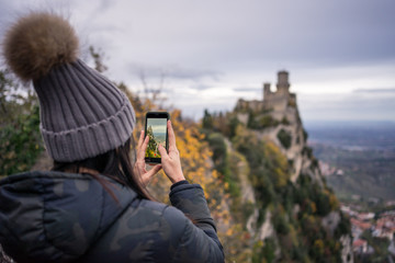 Back view of woman in hat with pompom and jacket taking photo on mobile phone of amazing place in San Marino, Italy