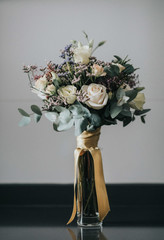 Glass vase with bunch of white roses and wild flowers placed on table against gray wall