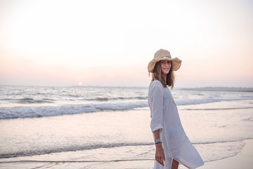 Relaxed graceful woman with long hair in hat and light white shirt on seaside under wavy water on beach