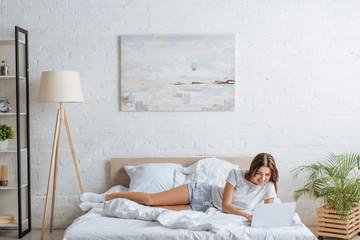 Fototapeta happy woman using laptop while relaxing in bedroom obraz