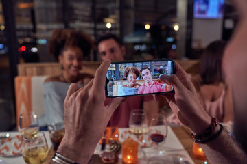Crop male hands photographing multiethnic couple in casual clothing on mobile phone while sitting at festive table at restaurant