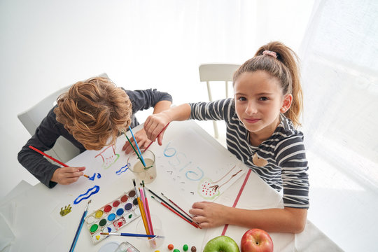 Concentrated girl and boy in casual outfit painting with watercolor while sitting at table at home