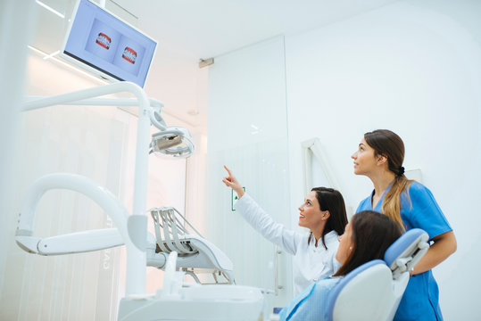 Side view of patient in chair and dentist with assistant in uniform pointing on picture explaining teeth structure