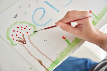 From above anonymous child painting tree on paper sheet while sitting at table at home