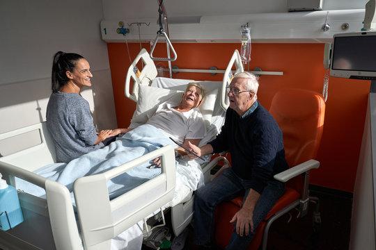 Husband and daughter visiting senior woman in hospital