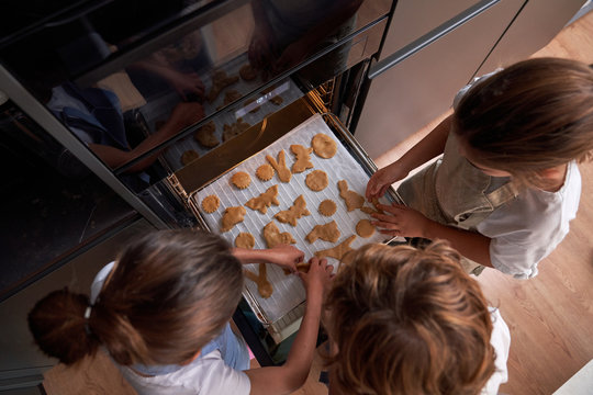From above of faceless children in aprons spreading cookies on cookie sheet in oven at modern kitchen