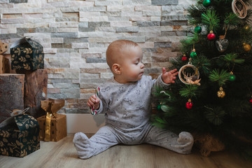 Cute baby with candy cane sitting on floor near stack of presents and playing with Christmas tree decoration during holiday celebration Fototapete