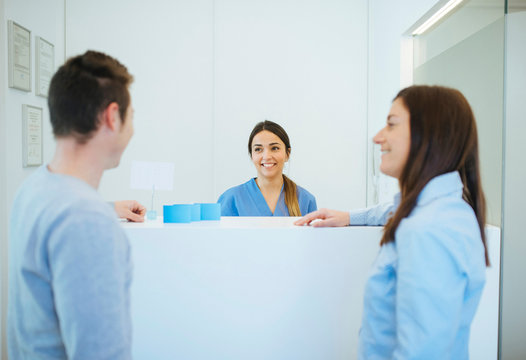 Side view of smiling client talking to man at reception desk across enthusiastic administrator in dental clinic