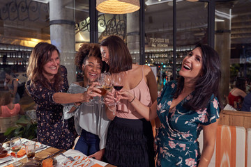 Multiethnic joyful female friends in casual clothing laughing while standing and proposing toast at stylish restaurant