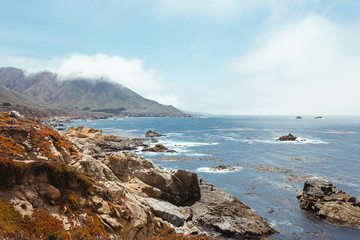 Empty stony rocky shore and clean blue water under light cloudy sky in Big Sur Fotobehang