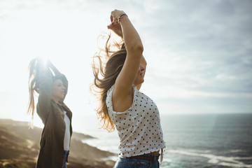 Side view of young women in back lit raising hands and holding hair over heads while standing together at seaside and enjoying fresh breeze and freedom