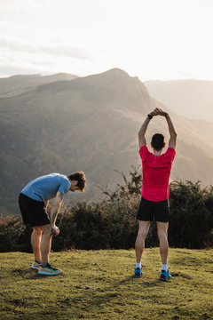 Back view of tired male joggers in blue and red shirts stretching after running and training hard while standing on top of green hill with beautiful mountain landscape in background