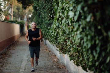 Smiling active mature man in good sportive shape jogging in narrow street along houses and botanical fence in summer day