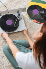 selective focus of vintage record player near girl sitting on carpet