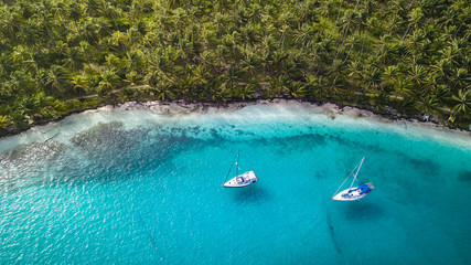 San Blas Islands, Panama - Aerial Drone Top Down View of two Sailing Yachts anchored in Turquoise Water right next to perfect White Sand Beach of Caribbean Tropical Island full of green Palm Trees. Wall mural
