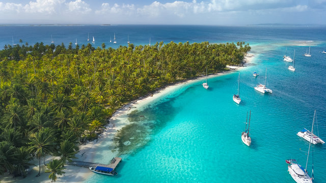 San Blas Islands, Panama - Drone Aerial View of many Sailboats & Sailing Yachts anchored in turquoise Water of Blue Lagoon next to white Sand Beach of Tropical Caribbean Island with green Palm Trees.