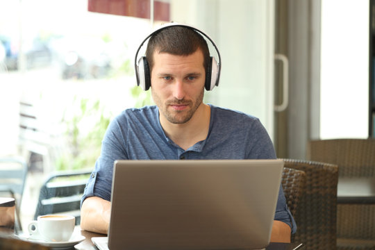 Front view of adult man using laptop and headphones